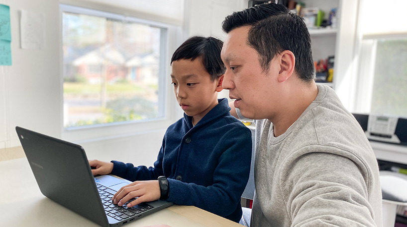 An adult working with their student at home